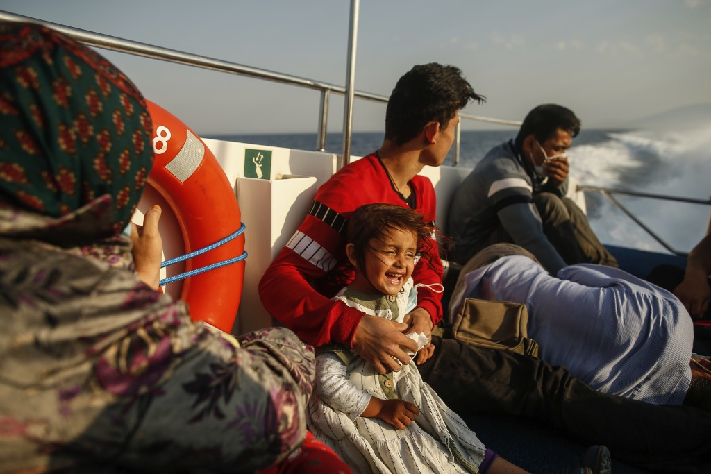 Migrants sit on a Turkish coast guard vessel after they were pulled off life rafts, during a rescue operation in the Aegean Sea, between Turkey and Gr...