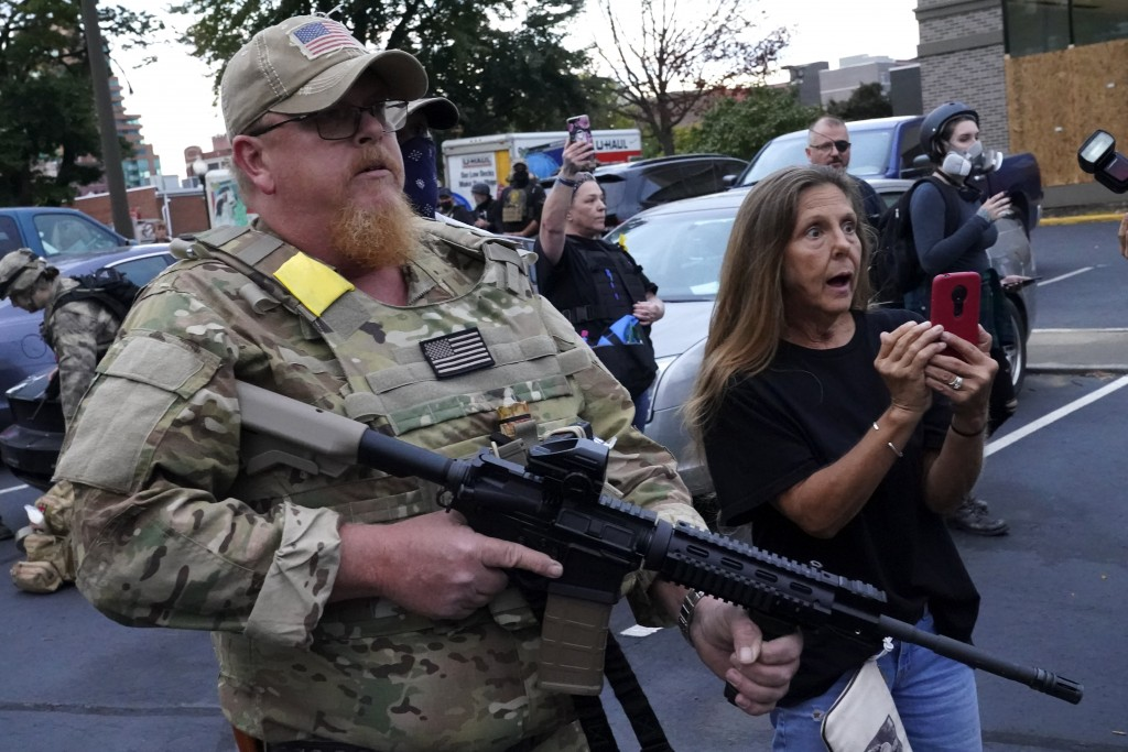 An armed counter-protester speaks with Black Lives Matter demonstrators, Thursday, Sept. 24, 2020, in Louisville, Ky. Authorities pleaded for calm whi...
