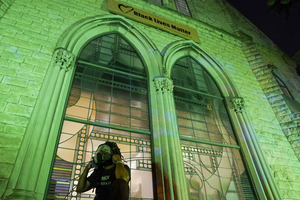 A protester wears a gas mask outside The First Unitarian church, Thursday, Sept. 24, 2020, in Louisville, Ky. Authorities pleaded for calm while activ...