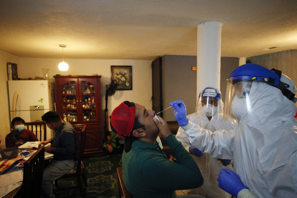 Dr. Ivan Mandujano, right, and nurse Alejandro Ramirez, conduct COVID-19 testing on seven members of the Moreno family, in their home in the Xochimilc...