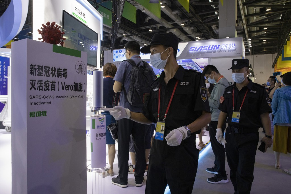 Chinese security guard walk past a giant replica of the COVID-19 vaccine produced by Sinopharm subsidiary CNBG displayed during a trade fair in Beijin...