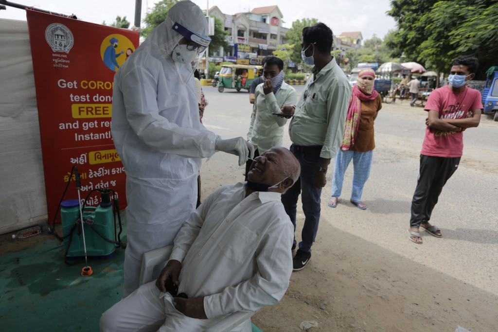 A health worker takes a nasal swab sample to test for COVID-19 test in Ahmedabad, India, Saturday, Sept. 26, 2020. The nation of 1.3 billion people is...