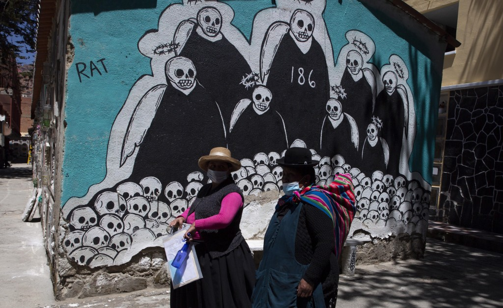 FILE - In this Sept. 23, 2020 file photo, women walk past a mural symbolizing death, on their way to the grave of a relative who died from complicatio...