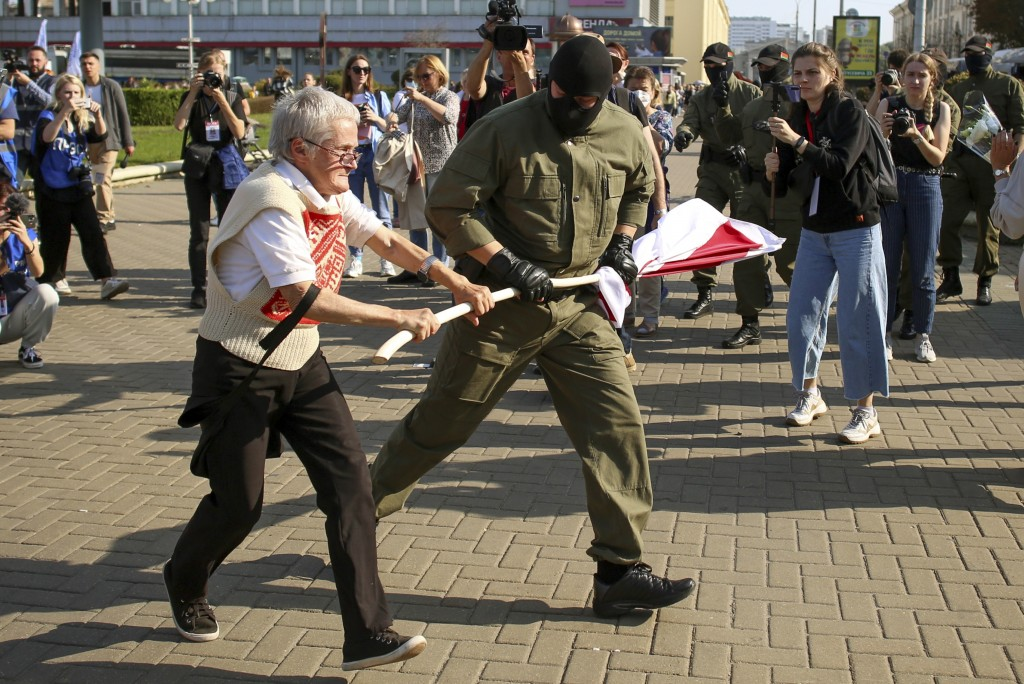 A police officer tries to take away an old Belarusian national flag from Nina Bahinskaya's hands during an opposition rally to protest the official pr...