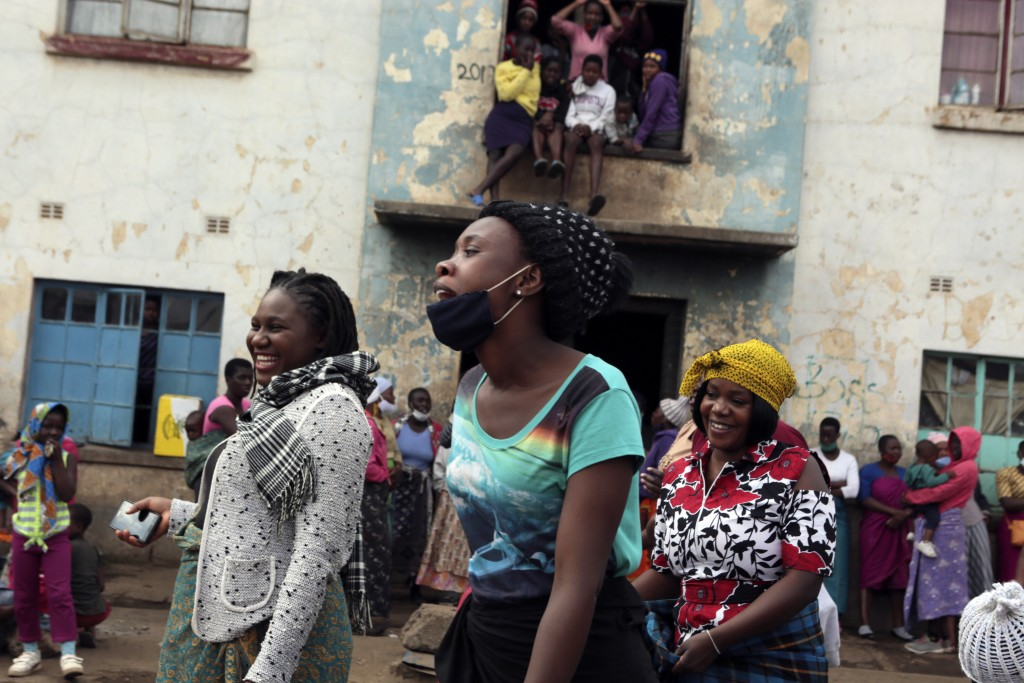Women share a light moment while attending a social gathering in a poor neighbourhood in Mbare, Harare, Friday, Sept,18, 2020. As Zimbabwe's coronavir...