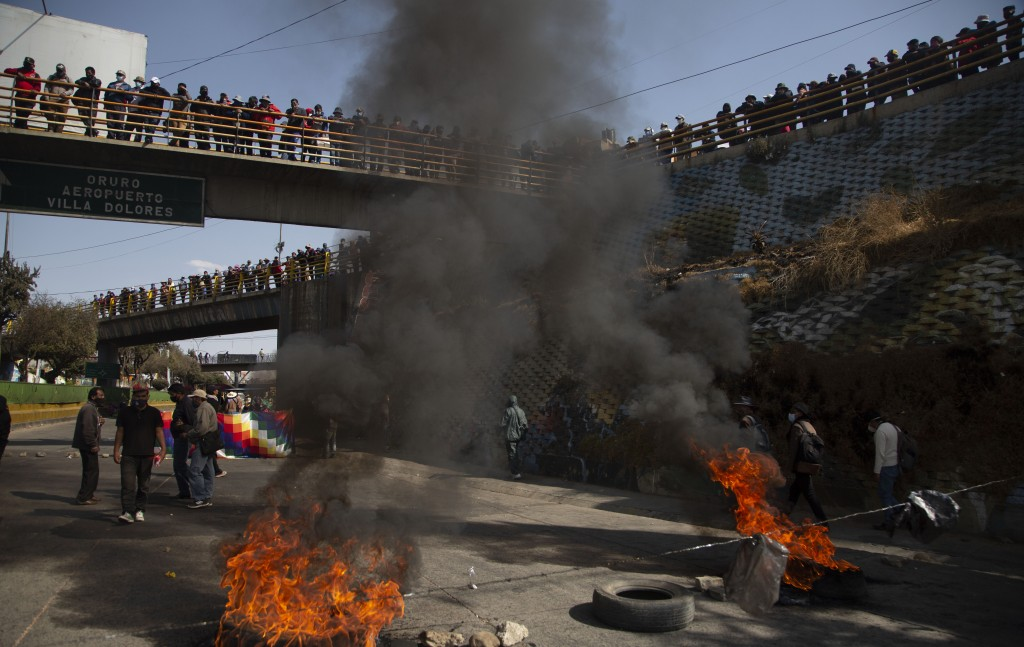 FILE - In this Aug. 10, 2020 file photo, demonstrators burn tires to protest the postponement of the upcoming presidential election in El Alto, Bolivi...