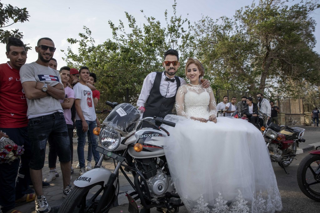 FILE - In this April 16, 2020 file photo, newlyweds are surrounded by their friends as they celebrate before a curfew imposed as a prevention measure ...