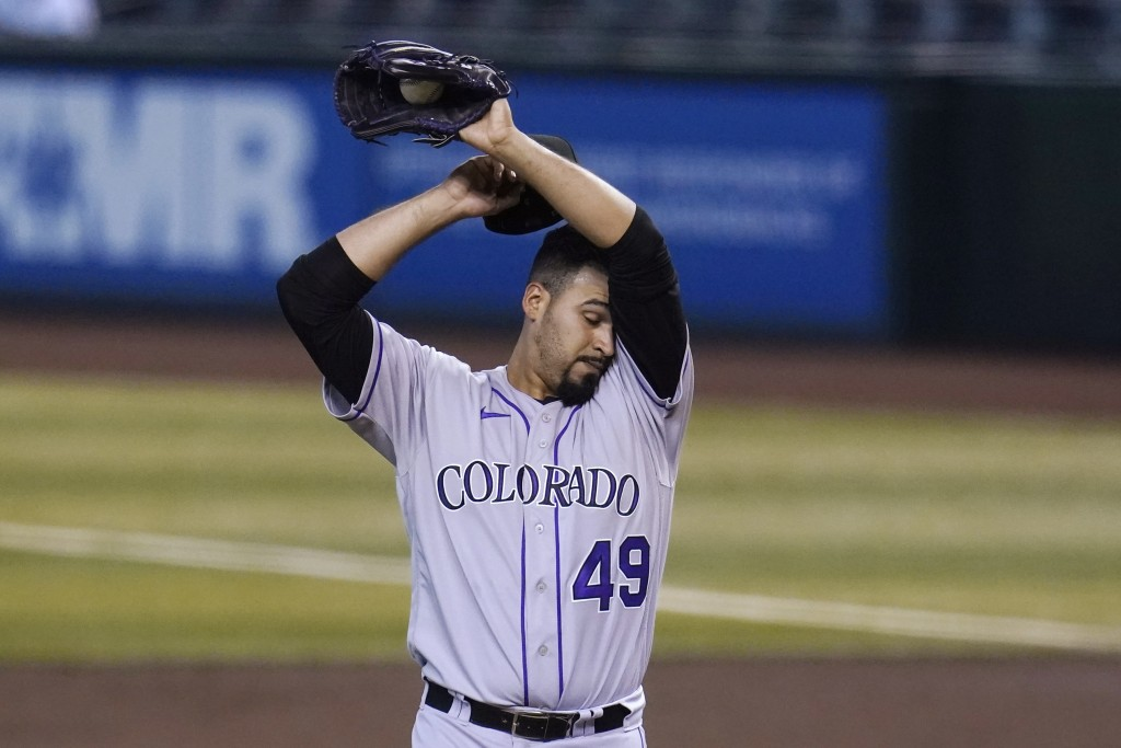 Colorado Rockies starting pitcher Antonio Senzatela wipes sweat from his face after giving up a two-run home run to Arizona Diamondbacks' Christian Wa...