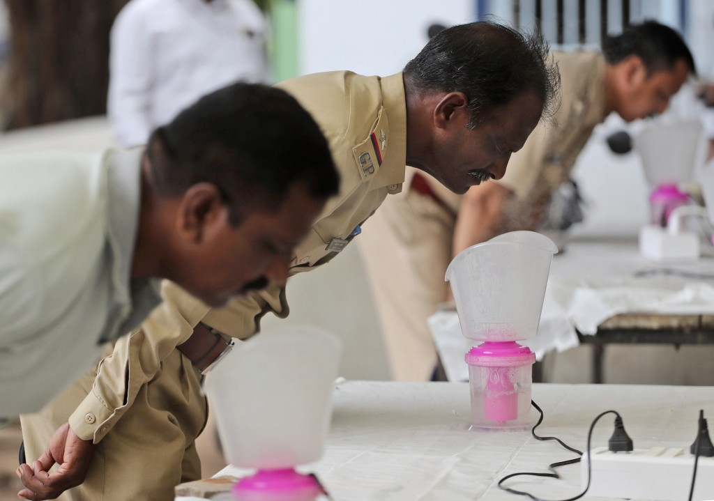 Indian policemen inhale steam at steam stations set up outside the office of the Commissioner of Police as a precautionary measure against the coronav...