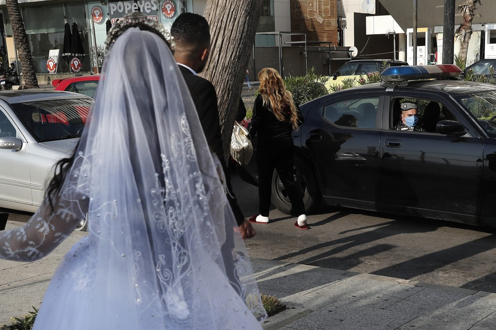 FILE - In this April 18, 2020 file photo, a policeman asks a bride and groom to leave the waterfront promenade where they had decided to take some pic...