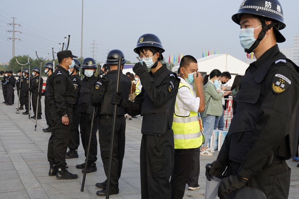 Security guards wearing masks and armed with restrainers stand guard at the entrance to the Auto China 2020 show in Beijing, China on Saturday, Sept. ...