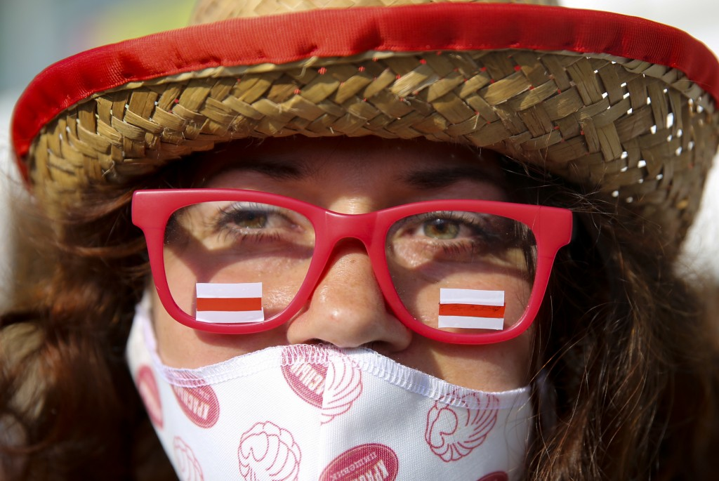 A woman wearing a face mask to protect agains coronavirus and a glasses with stickers in an old Belarusian national flag colors attends an opposition ...