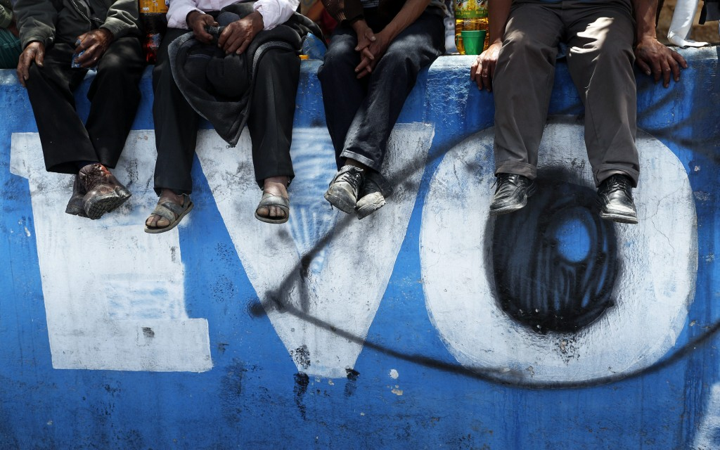 FILE - In this Nov. 17, 2019 file photo, supporters of former President Evo Morales sit over a mural emblazoned with his first name, in Sacaba, Bolivi...