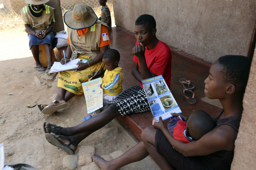 Community health worker, Rosemary Rambire, left, takes notes during a COVID-19 awareness campaign in Chitungwiza, on the outskirts of Harare, Wednesda...