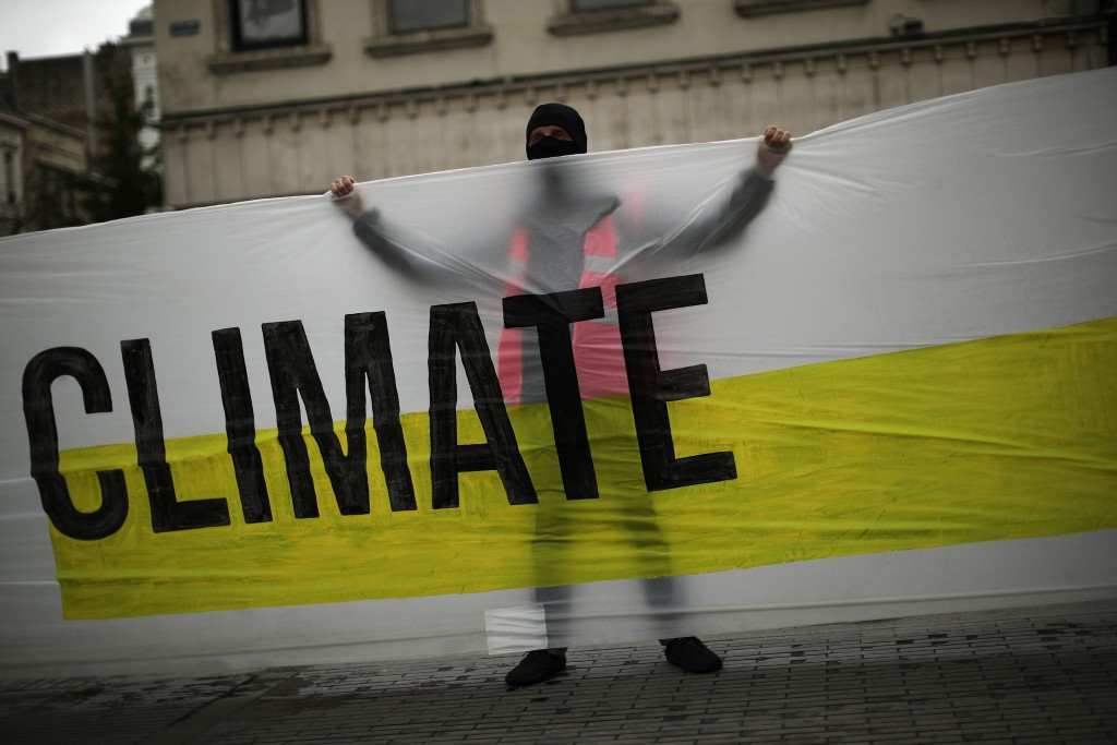 """A man, wearing a mask to prevent the spread of the coronavirus, holds a banner that reads: """"United for climate"""" during a small climate change protest ..."""
