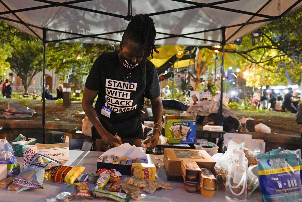 Rose Henderson helps out at a booth in Jefferson Square Park, Thursday, Sept. 24, 2020, in Louisville, Ky. A grand jury has indicted one officer on cr...