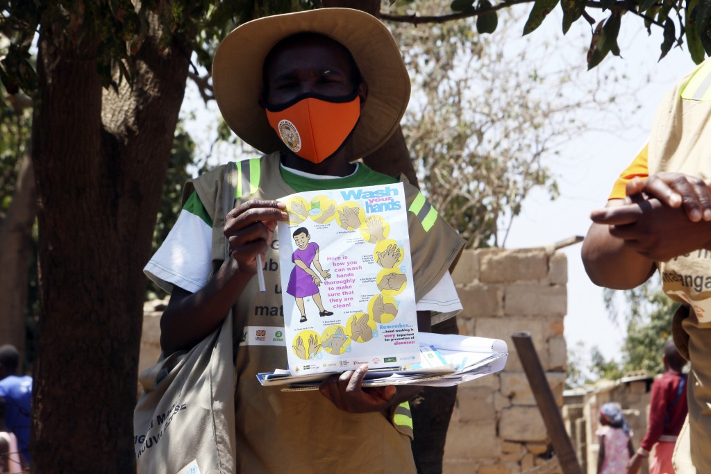 A community health worker holds a pamphlet during a COVID-19 awarness campaign in Chitungwiza on the outskirts of Harare, Wednesday, Sept. 23, 2020. A...