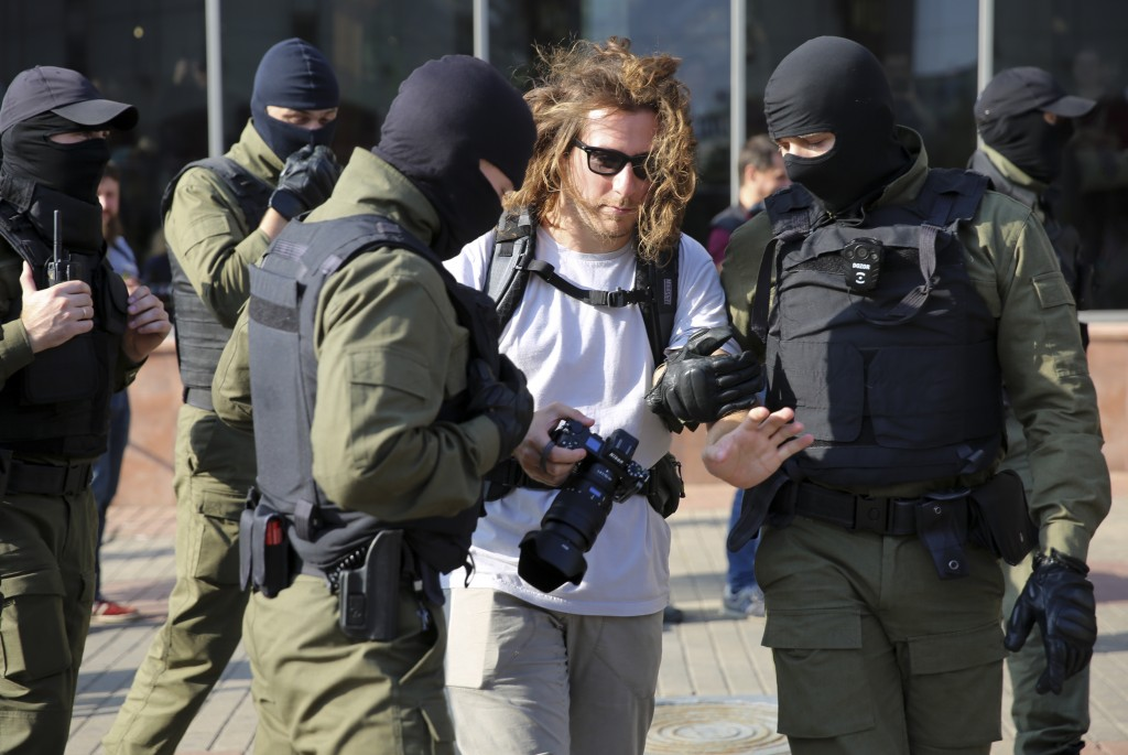 Police officers detain a photojournalist during an opposition rally to protest the official presidential election results in Minsk, Belarus, Saturday,...