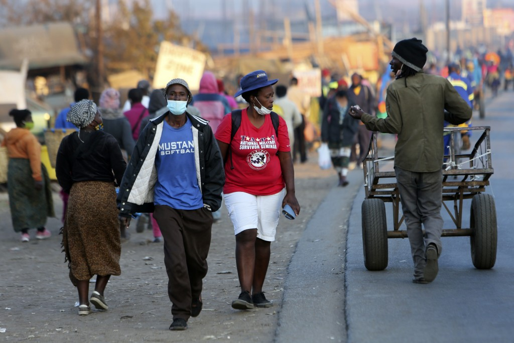 People wear face masks to protect against coronavirus, in Harare, Monday, Sept. 21, 2020. As Zimbabwe's coronavirus infections decline, strict lockdow...