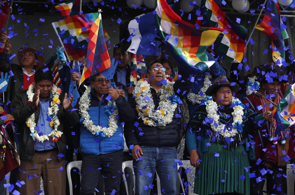 FILE - In this Feb. 8, 2020 file photo, confetti showers Luis Arce, center, Bolivian presidential candidate for the Movement Towards Socialism Party, ...