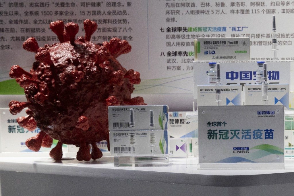 Samples of a COVID-19 vaccine produced by Sinopharm subsidiary CNBG are displayed near a 3D model of a coronavirus during a trade fair in Beijing on S...