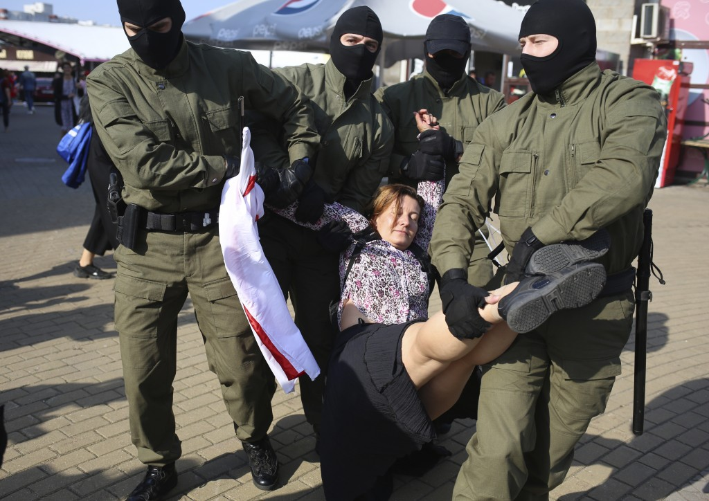 Police officer detain a woman with an old Belarusian national flag during an opposition rally to protest the official presidential election results in...