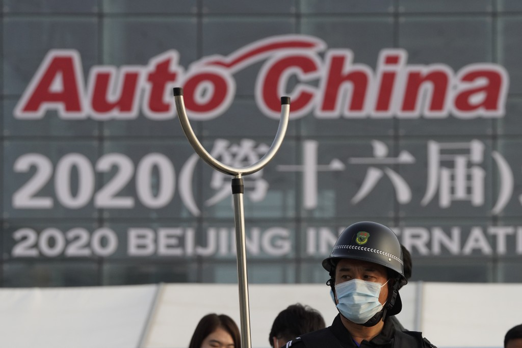 A security guard wearing mask and armed with a restrainer stands guard at the entrance to the Auto China 2020 show in Beijing, China on Saturday, Sept...