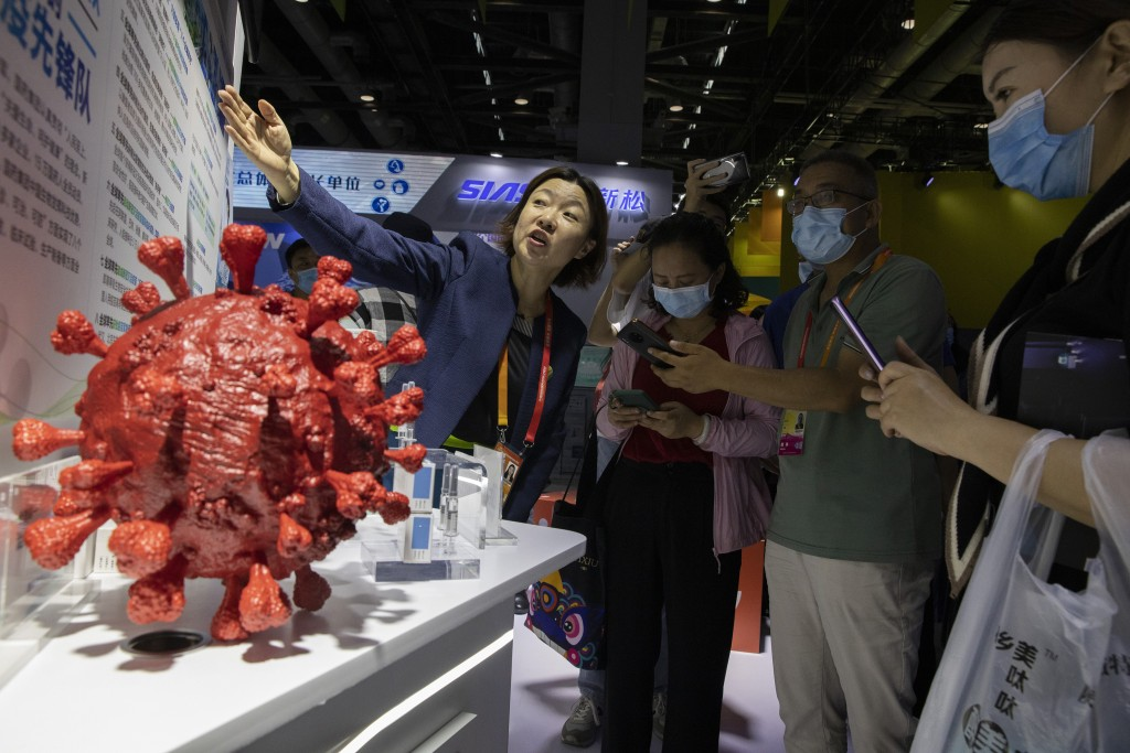 An employee answers questions from the public near samples of a COVID-19 vaccine produced by Sinopharm subsidiary CNBG are displayed during a trade fa...