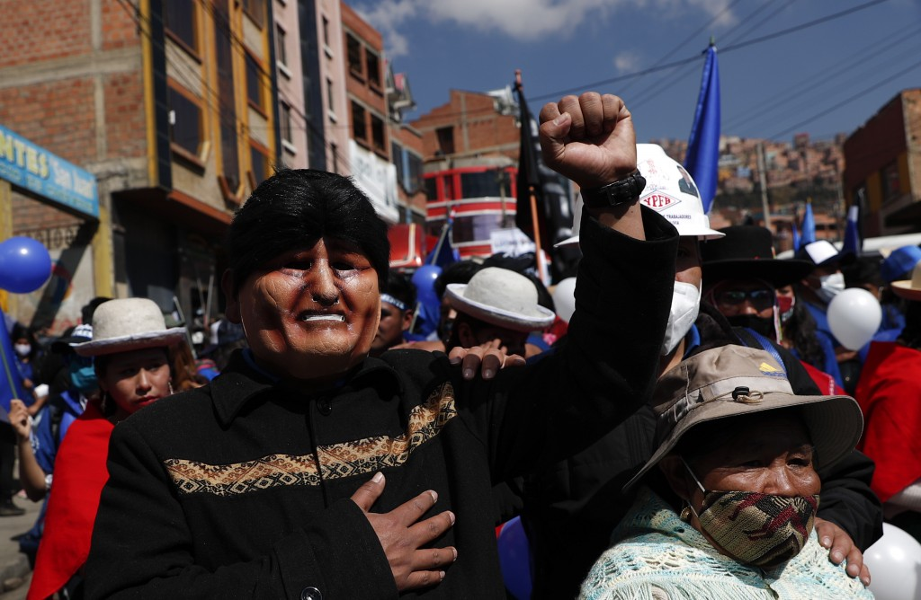 FILE - In this Sept. 19, 2020 file photo, a supporter, wearing a mask depicting former President Evo Morales, strikes a pose during a campaign rally f...