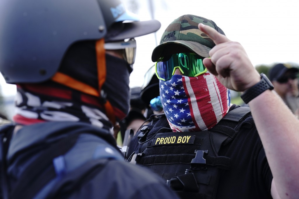 A right-wing demonstrator, right, gestures toward a counter protester as members of the Proud Boys and other right-wing demonstrators rally on Saturda...