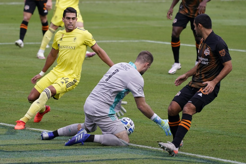 Houston Dynamo goalkeeper Marko Maric (1) makes a stop in front of Nashville forward Daniel Rios (14) during the first half of an MLS soccer match Sat...