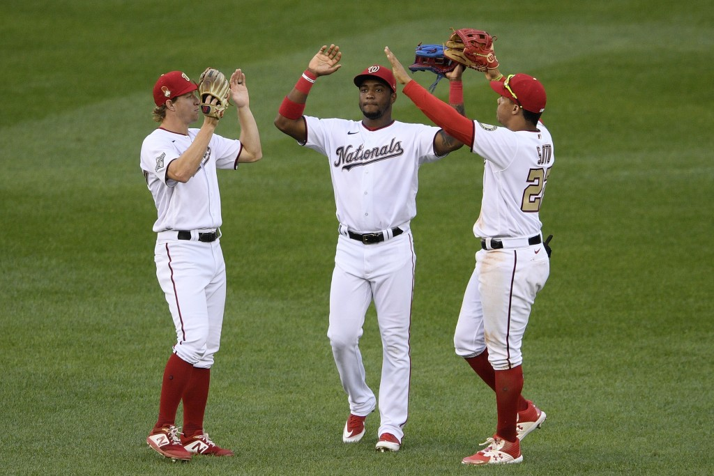 Washington Nationals outfielders Victor Robles, center, Andrew Stevenson, left, and Juan Soto, right, celebrate after the first baseball game of a dou...