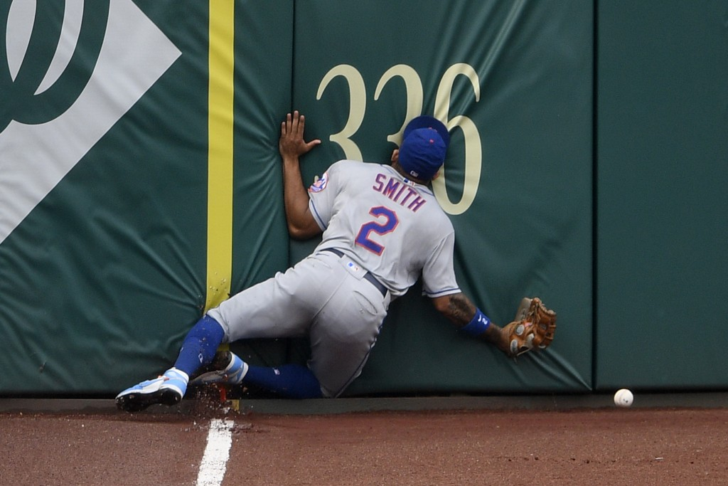 New York Mets' Dominic Smith smashes into the outfield wall while chasing a fly ball that went for an inside-the-park home run by Washington Nationals...