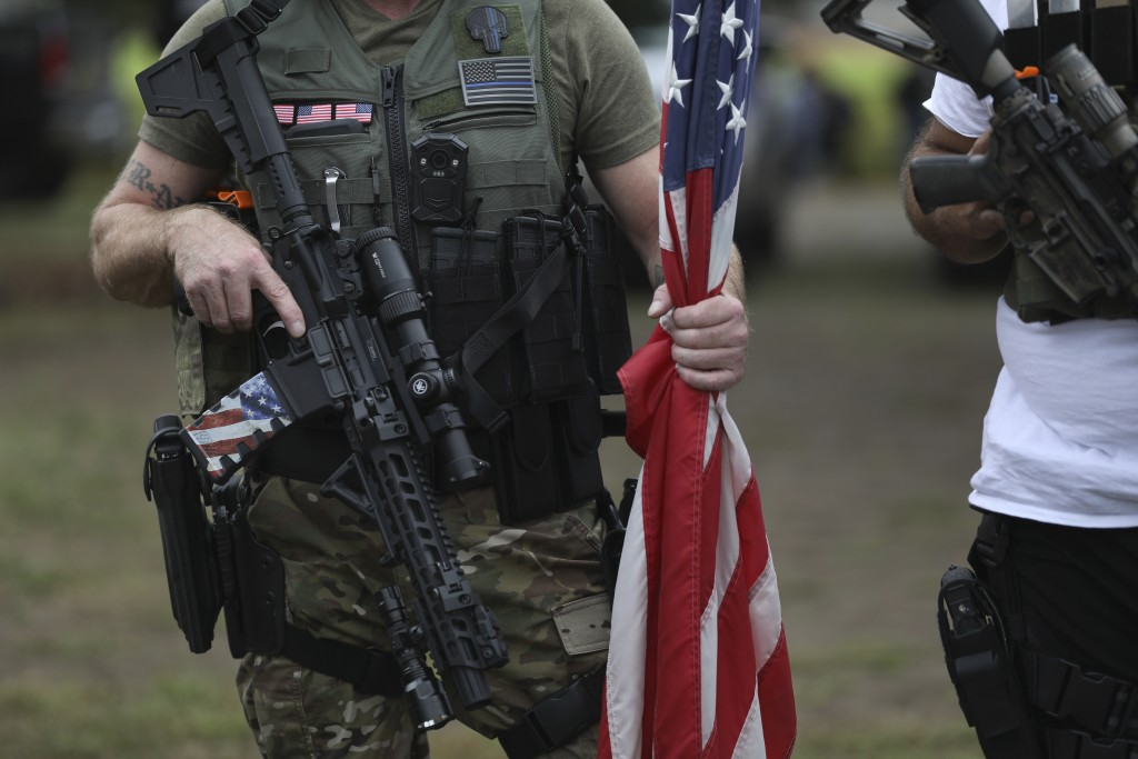 A person holds a weapon and a flag as members of the Proud Boys and other right-wing demonstrators rally on Saturday, Sept. 26, 2020, in Portland, Ore...