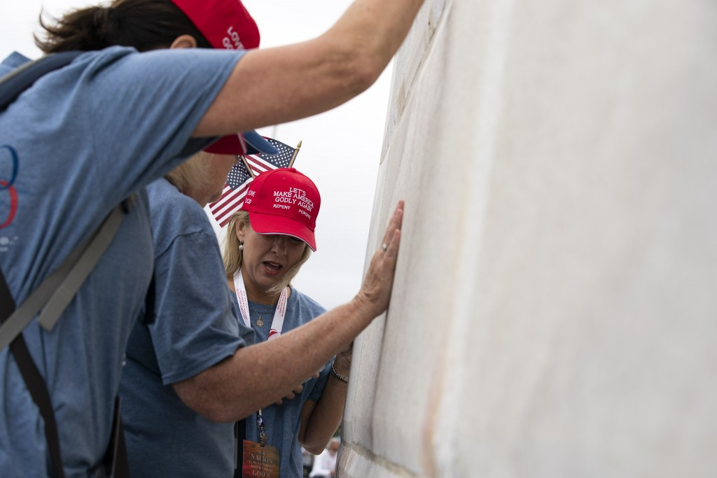 Followers of Franklin Graham pray at the base of the Washington Monument as they march from the Lincoln Memorial to Capitol Hill, during the Prayer Ma...