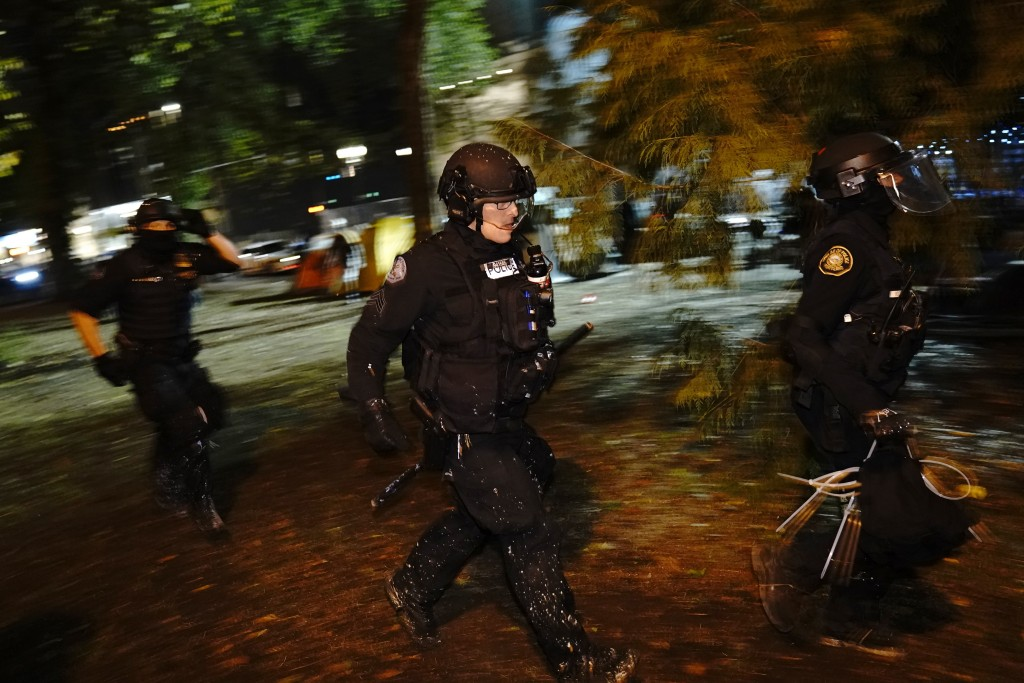 Portland police run through a park during protests, Saturday, Sept. 26, 2020, in Portland. The protests which began since the police killing of George...