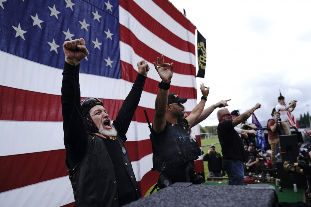 Members of the Proud Boys cheer on stage as they and other right-wing demonstrators rally, Saturday, Sept. 26, 2020, in Portland, Ore. (AP Photo/John ...