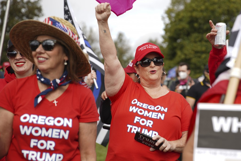 Women cheer as members of the Proud Boys and other right-wing demonstrators rally on Saturday, Sept. 26, 2020, in Portland, Ore. (AP Photo/Allison Din...