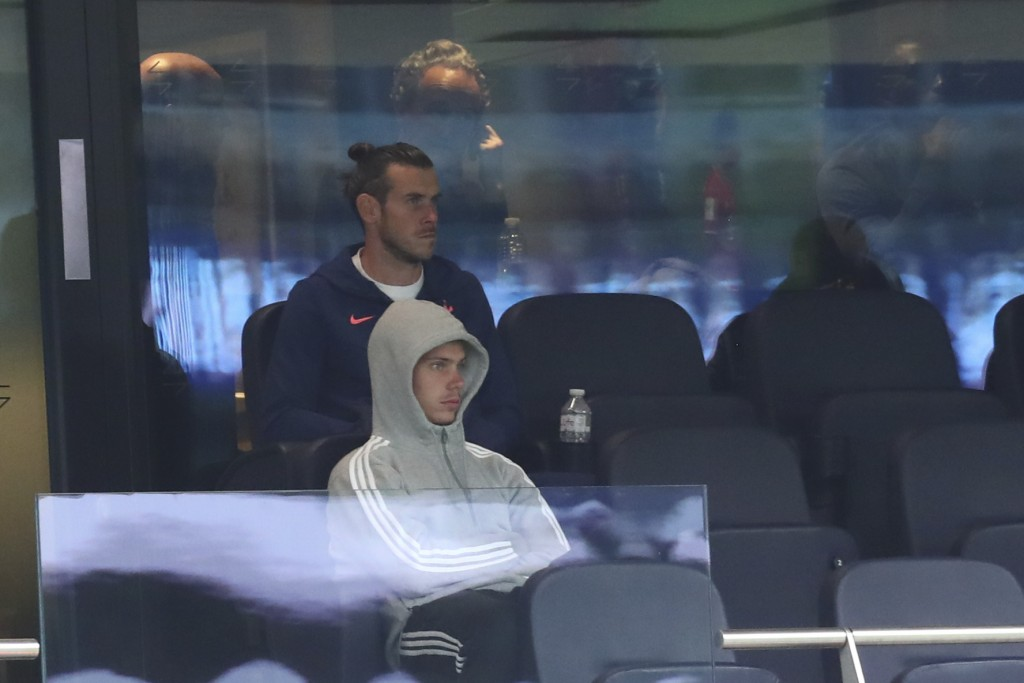 Tottenham's Gareth Bale, backfround, sits on the stands during the English Premier League soccer match between Tottenham and Newcastle at the Tottenha...