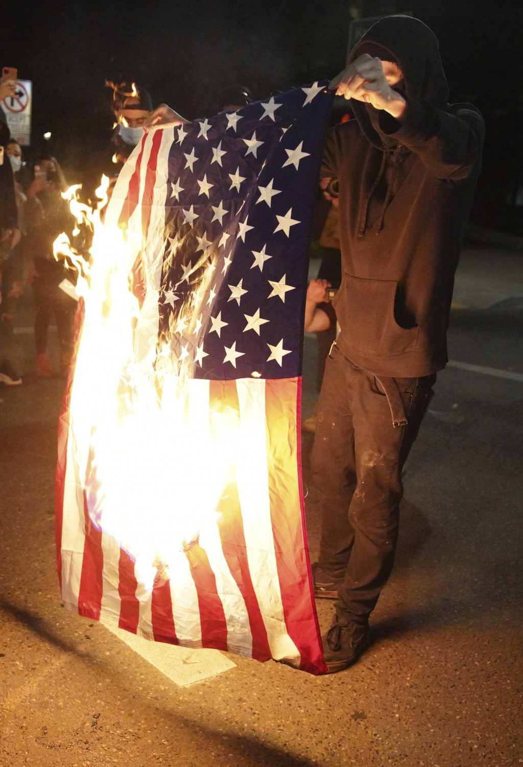 A protester burns an American flag while rallying at the Mark O. Hatfield United States Courthouse on Saturday, Sept. 26, 2020, in Portland, Ore. The ...
