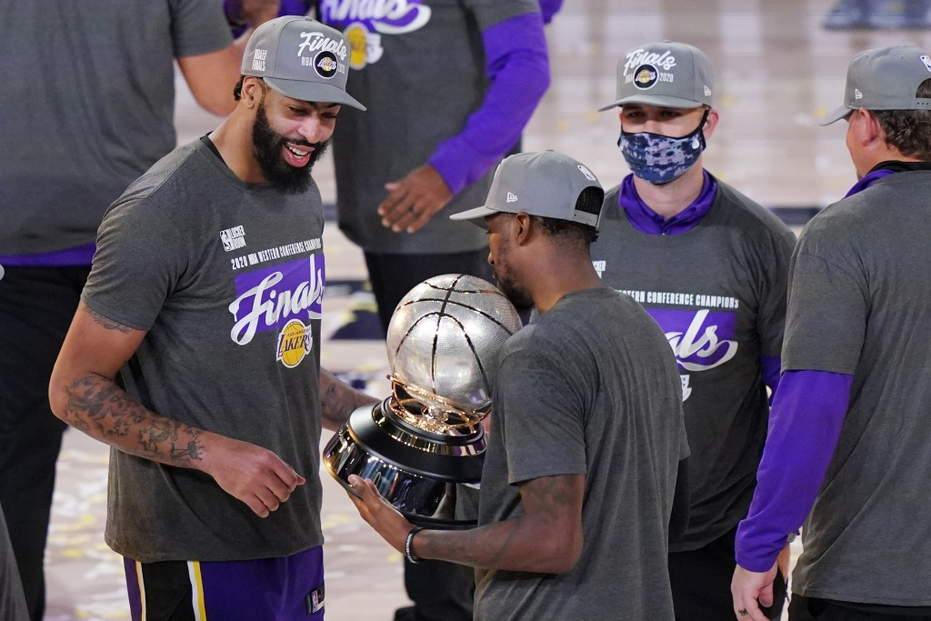Los Angeles Lakers' Anthony Davis, left, looks at their trophy after beating the Denver Nuggets in an NBA conference final playoff basketball game Sat...