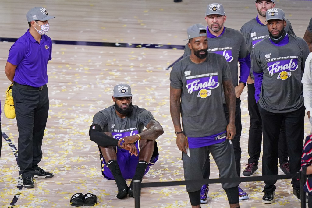 Los Angeles Lakers' LeBron James sits on the floor as he waits for the trophy ceremony to start after the Lakers beat the Denver Nuggets in an NBA con...