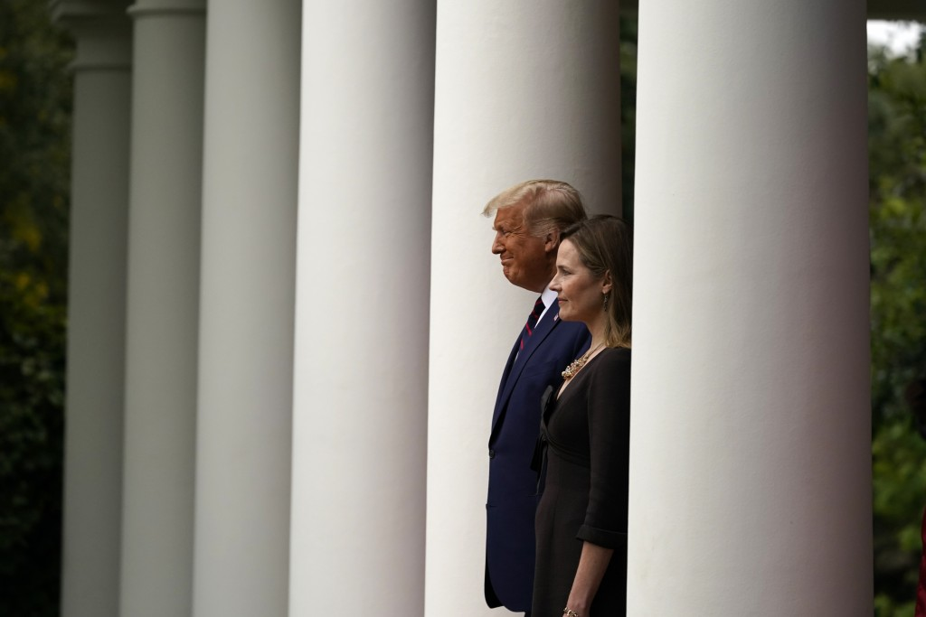 President Donald Trump walks with Judge Amy Coney Barrett to a news conference to announce Barrett as his nominee to the Supreme Court, in the Rose Ga...