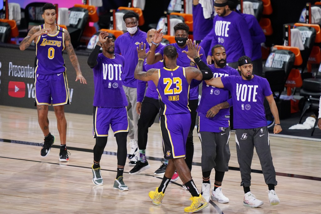 Los Angeles Lakers' LeBron James (23) celebrates with teammates during a timeout in the final moments of an NBA conference final playoff basketball ga...