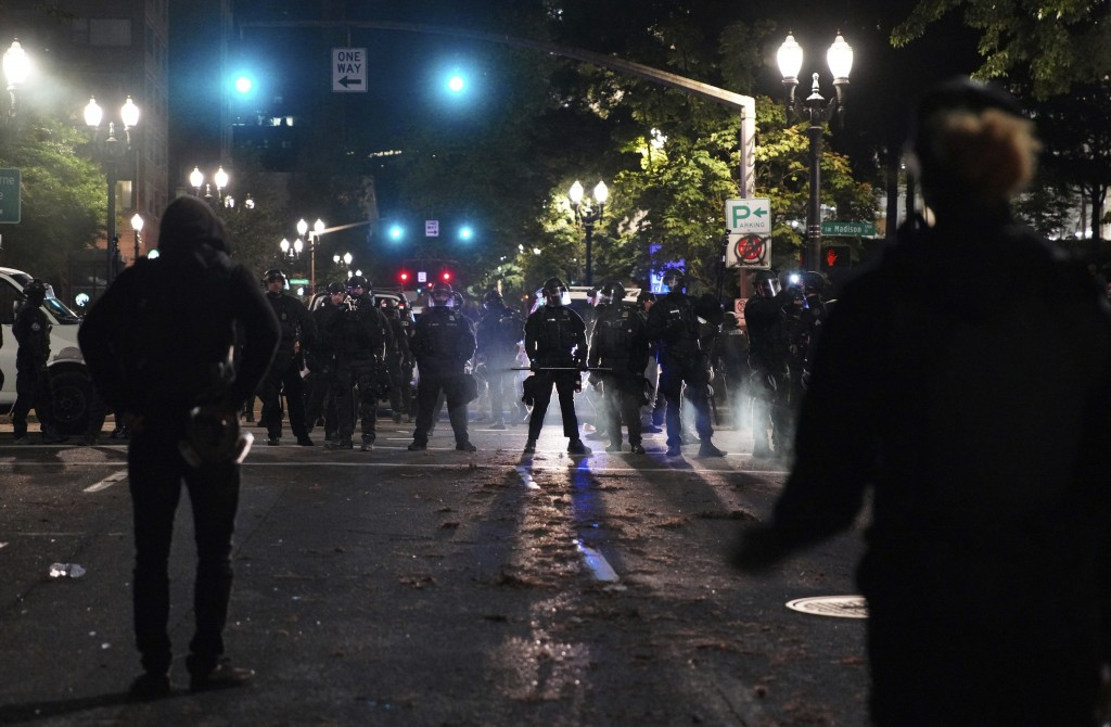 Portland Police line up blocking the street while protesters rally in front of them at the Mark O. Hatfield United States Courthouse on Saturday, Sept...