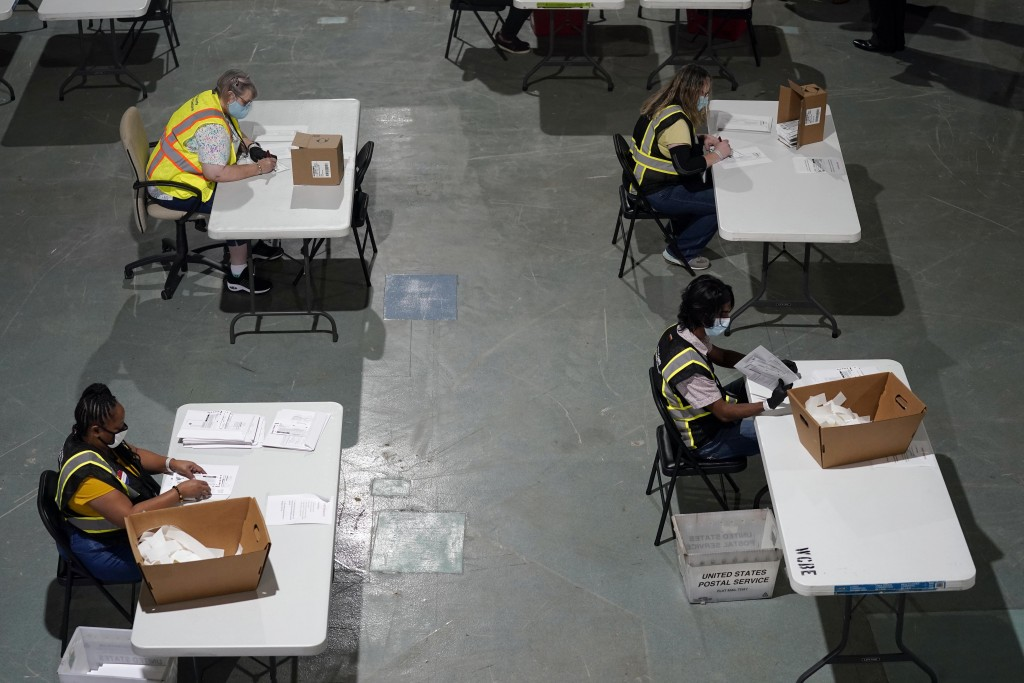 FILE - In this Thursday, Sept. 3, 2020 file photo, workers prepare absentee ballots for mailing at the Wake County Board of Elections in Raleigh, N.C....