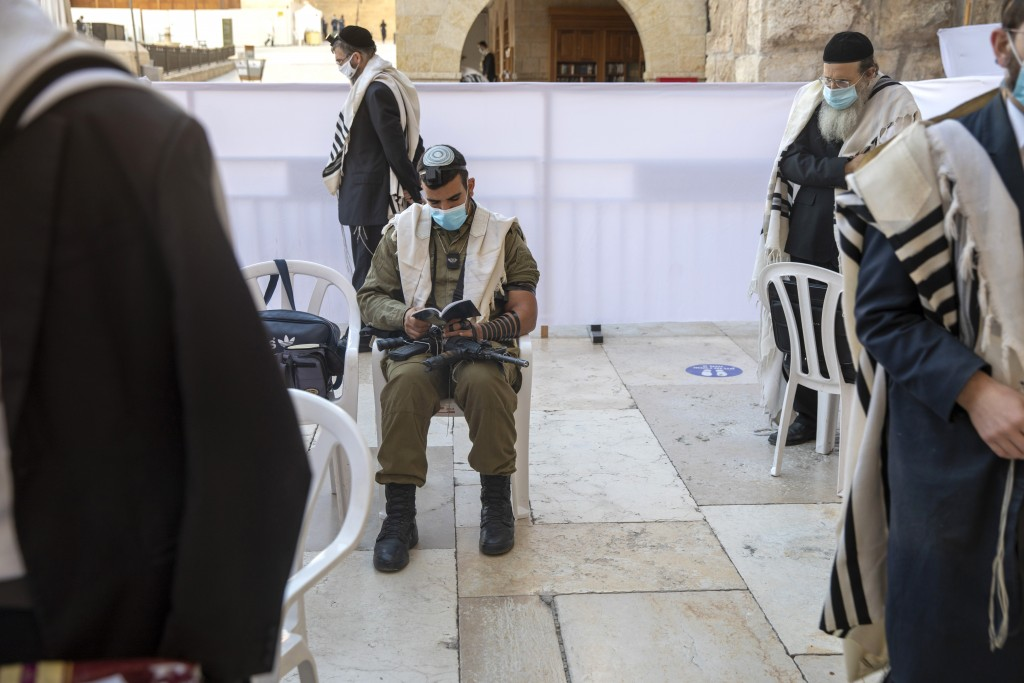With social distancing, an Israeli soldier and ultra-Orthodox Jewish men pray ahead of Yom Kippur, the holiest day in the Jewish year which starts at ...