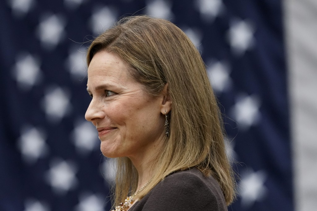 Judge Amy Coney Barrett listens as President Donald Trump announces Barrett as his nominee to the Supreme Court, in the Rose Garden at the White House...
