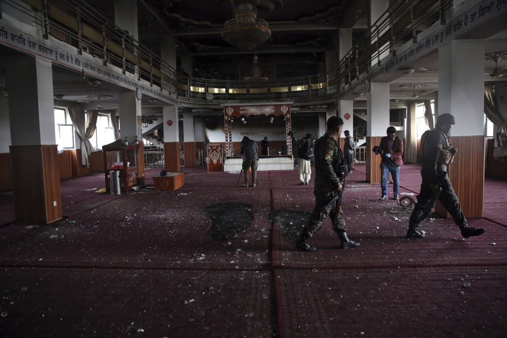 FILE- in this Wednesday, March 25, 2020 file photo, Afghan security personnel and journalists inspect the inside a Sikh house of worship, after an att...