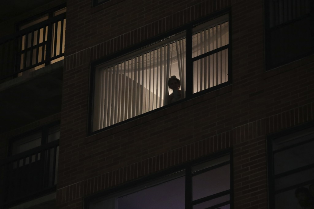 A woman looks out her window while protesters and police clash near the Mark O. Hatfield United States Courthouse on Saturday, Sept. 26, 2020, in Port...
